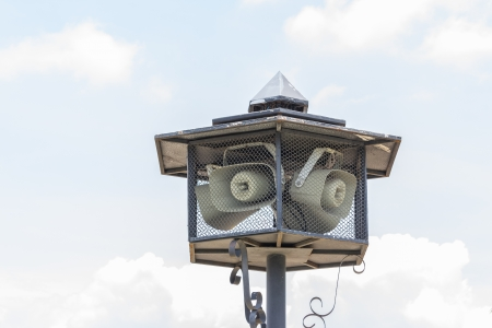 public address: Outdoor public address loudspeakers against a blue sky