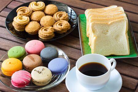 macarons, brood, koekjes en zwarte koffie op tafel Stockfoto