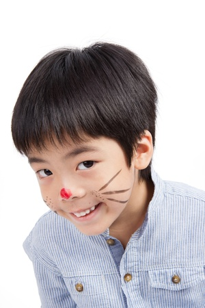 cute boy painting his face smiling isolated on white background Stock Photo