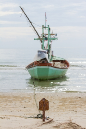 small anchor of fishing boat at the beach photo