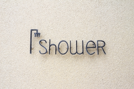 woman bath: shower sign on sand wall Editorial
