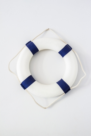 white and blue lifebuoy hanging on white wall Stock Photo