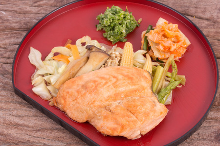 Salmon steak with vegetables on wooden background photo