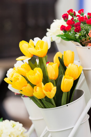 artificial yellow tulips in white pot