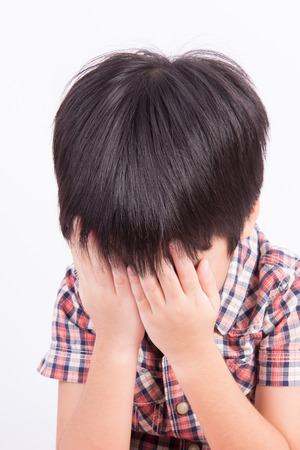 Young little boy crying or playing with hiding face photo