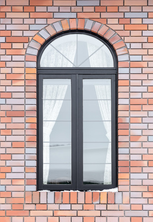 painted wood arched window in a red brick wall