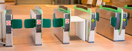 Turnstiles in underground railway station. Green arrows pointing to the way forwards. green barriers preventing progress Stock Photo