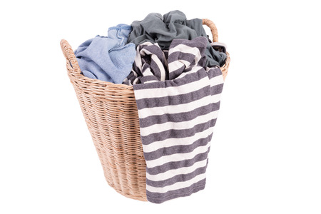 Clothes in a laundry wooden basket isolated on white background photo