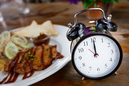 lunch time: Clock on Wooden Table with steak on , Lunch Time Concept