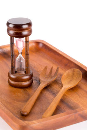 pass away: Hourglass on a plate with a fork and knife for food and time conceptual themes. Stock Photo