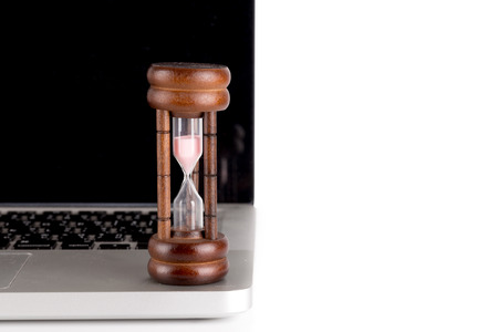 hourglass with laptop - time concept photo