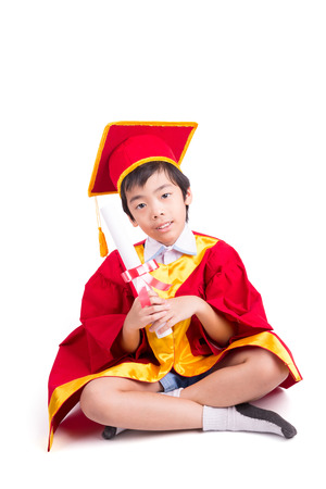 toga y birrete: Little Boy lindo que desgasta el vestido rojo Kid Graduaci�n Con Birrete Y Certificado Kindergarten En La Mano Aislado Sobre Fondo Blanco Foto de archivo