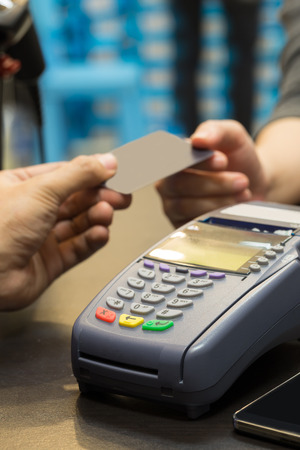 trade credit: Credit Card Machine On The Table with Hand Paying by Credit Card