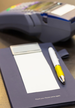 the word Thank you on credit card receipt writing pad with blank paper and credit card machine in background 版權商用圖片