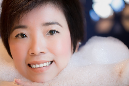 woman in bath: Close-up of beautiful young woman takes bubble bath : Selective Focus