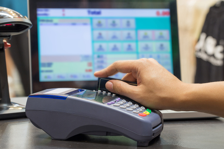 efectivo: Mano de tarjeta de crédito Swiping En tienda