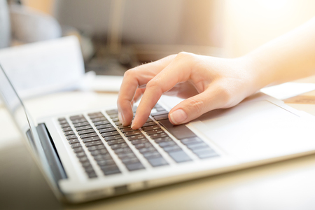 background information: Womans hands typing on laptop keyboard : Selective Focus Stock Photo