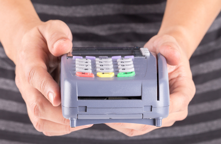 Cashier Holding Credit Card Machine