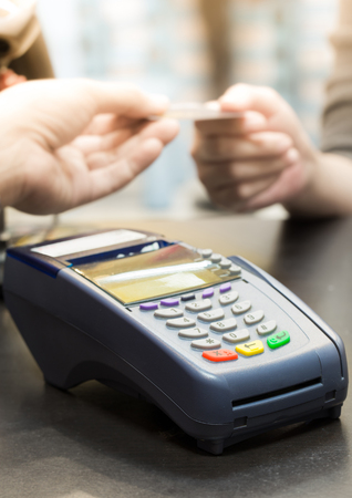 debit card: Credit Card Machine on the Table with Woman handing over credit card to Cashier in Background