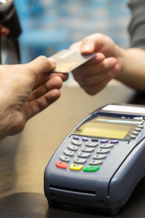pagando: Tarjeta de crédito automático en la tabla con mujer la entrega de la tarjeta de crédito al cajero en segundo plano