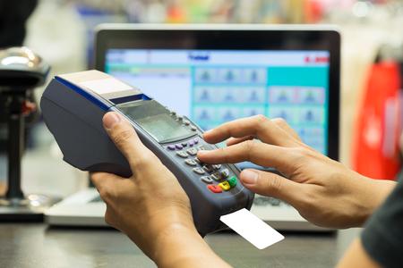 pagando: la mano del hombre con tarjeta de crédito pasen a través del terminal a la venta en la tienda