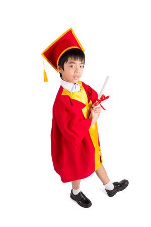 toga y birrete: Little Boy lindo que desgasta el vestido rojo Kid Graduaci�n Con Birrete Aislado Sobre Fondo Blanco