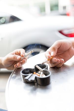 hombre fumando: El hombre que fuma el cigarrillo y el uso de un cenicero
