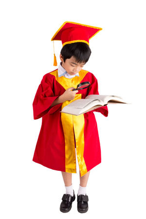 graduation cap and diploma: Portrait Of Curious Boy In Red Gown Kid Graduation With Mortarboard Looking A Book Through Magnifying Glass