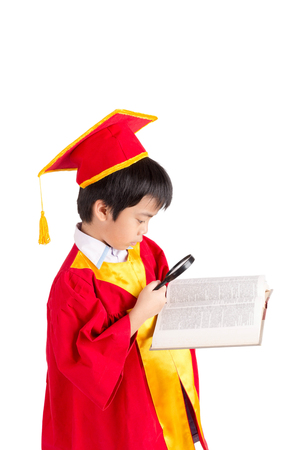cap and gown: Portrait Of Curious Boy In Red Gown Kid Graduation With Mortarboard Looking A Book Through Magnifying Glass