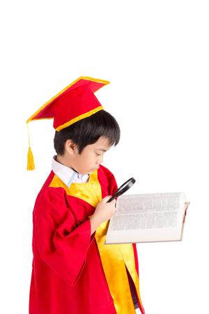 graduacion ni�os: Retrato Del Muchacho Curioso En Vestido Rojo Kid Graduaci�n Con Birrete Buscando un libro a trav�s de la lupa