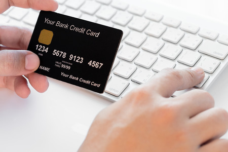 hand holding a credit card and typing. On-line shopping on the internet Stock Photo