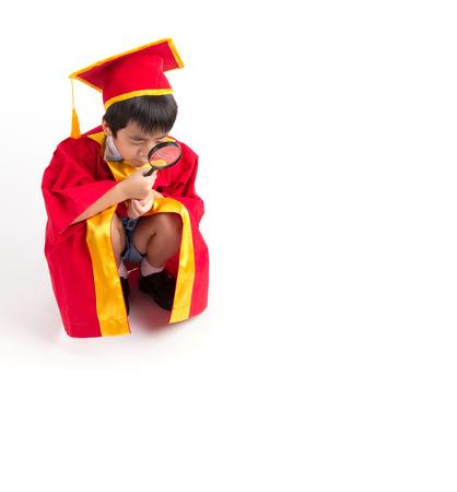 graduacion ni�os: Retrato de ni�o curioso en vestido rojo Kid graduaci�n con birrete buscando algo a trav�s de la lupa con Copyspace Foto de archivo