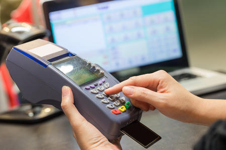 pagando: Mano de tarjeta de crédito Swiping En tienda
