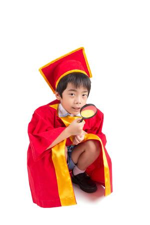 graduacion ni�os: Retrato Del Muchacho Curioso En Vestido Rojo Kid Graduaci�n Con Birrete Buscando algo a trav�s de la lupa Foto de archivo