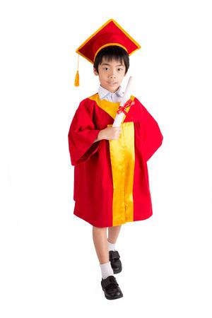 graduacion ni�os: Little Boy lindo que desgasta el vestido rojo Kid Graduaci�n Con Birrete Aislado Sobre Fondo Blanco