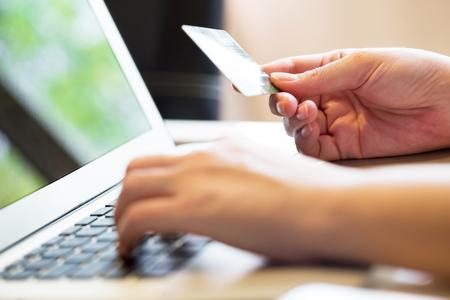compras: Mujer que sostiene la tarjeta de crédito en la computadora portátil para el concepto de las compras en línea