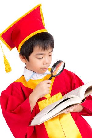 toga y birrete: Retrato Del Muchacho Curioso En Vestido Rojo Kid Graduaci�n Con Birrete Buscando un libro a trav�s de la lupa