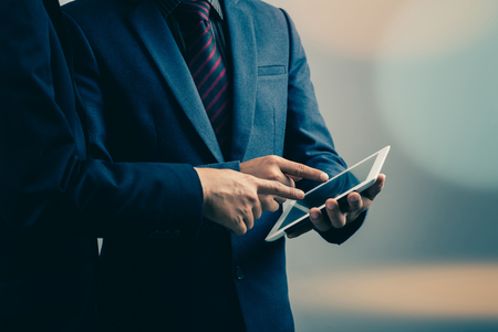 two businessmen using tablet-pc : filtered process Foto de archivo