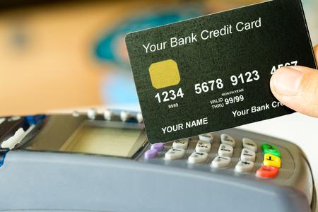 tarjeta de credito: mano que sostiene una tarjeta de crédito con la máquina de la tarjeta de crédito