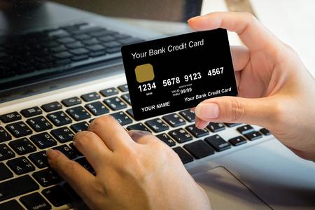 ノート パソコンのオンライン ショッピング概念上クレジット カードを持っている手
