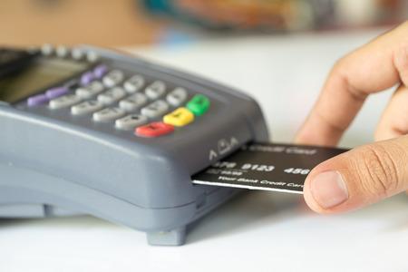 tarjeta de credito: La mano la tarjeta de crédito de empuje en una máquina de tarjeta de crédito: Enfoque diferencial
