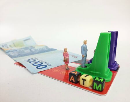 Simple Photo ilustration for Financial Transaction at Automatic Teller Machine, 50000 indonesia rupiah money and red card as a floor, pencil sharpener as a ATM machine, with word from plastic cube bead, white background