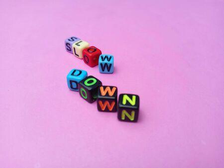 Photo Illustration, Word Slow Down from plastic alphabet cube beads Stockfoto