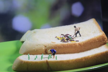 Photo close up top view Miniature Figure Farmer toy working  at Bread Stock Photo