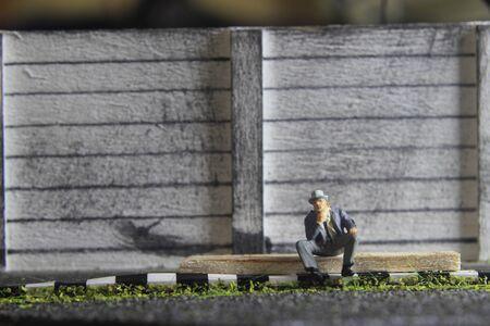 Photo Illustration, Hopeless Sad Old Man Mini Figure Toy Sitting at sidewalk, beside burned match stick represented as spirit Stock Photo