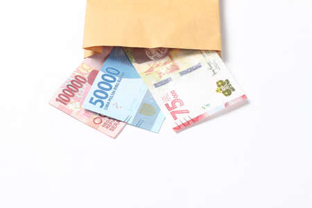 Random Layout Photo Rupiah Paper Money, 10000, 50000, 100000 and 75000 at Brown Envelope at White Background Stock fotó