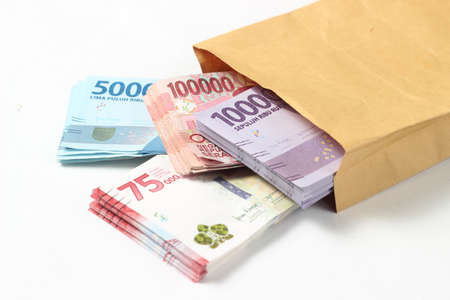 Random Layout Photo Rupiah Paper Money, 10000, 50000, 100000 and 75000 at Brown Envelope at White Background