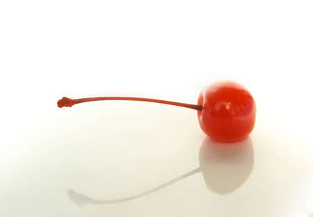 Red compoted cocktail cherry lying on the white background Stock Photo