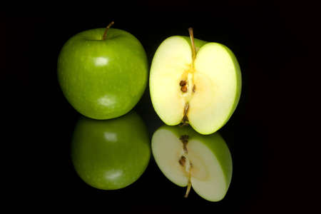 Shiny green apple and a half isolated on the shiny black background