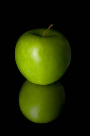 Shiny green apple isolated on the shiny black background